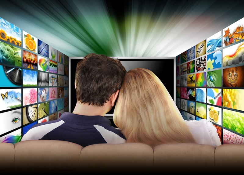 A couple is sitting on a couch watching a flat screen television with photo images coming out of the sides. The tv has a glowing light coming out the top. Use it for a media, entertainment, technology or date night concept.